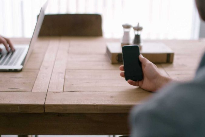 person-smartphone-office-table-676x450